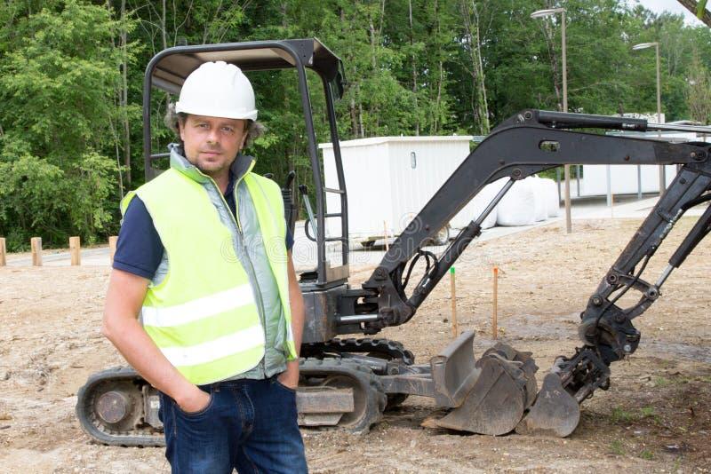 Motorista do homem da construção com a máquina escavadora no local exterior do fundo imagens de stock royalty free