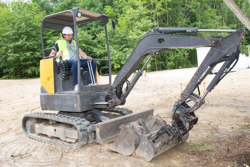 motorista do homem do operador na máquina escavadora no canteiro de obras fotografia de stock