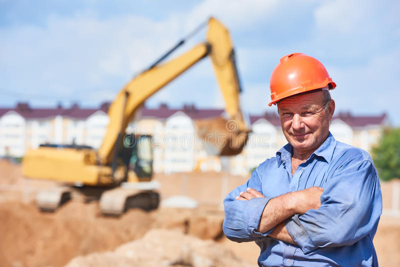 Motorista do trabalhador da construção na frente do carregador de máquina escavadora imagem de stock