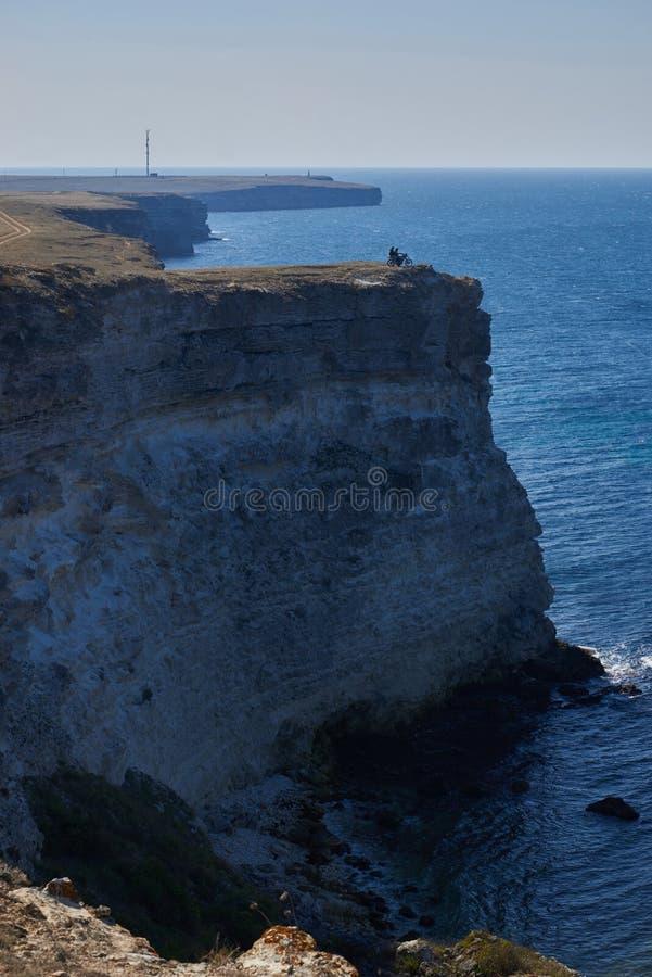 Motorista en el acantilado rocoso del mar imagen de archivo