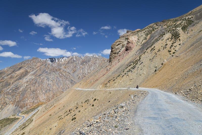 Motorista en el camino de la montaña fotografía de archivo