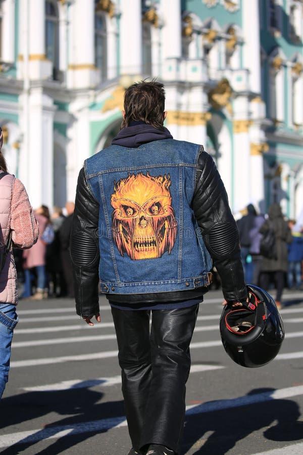 Motorista en un chaleco del dril de algodón con un applique abstracto del cráneo llevado sobre una chaqueta de cuero Visi?n poste imágenes de archivo libres de regalías