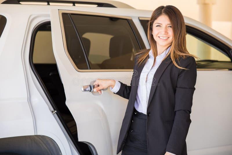 Motorista fêmea bonito que abre a porta de carro fotografia de stock