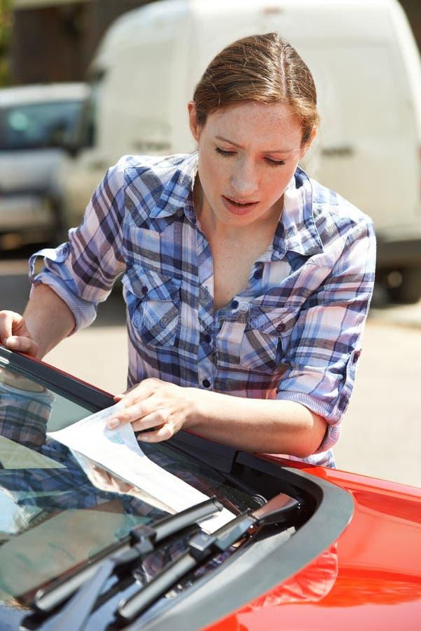 Motorista fêmea frustrante que olha o bilhete de estacionamento imagens de stock royalty free