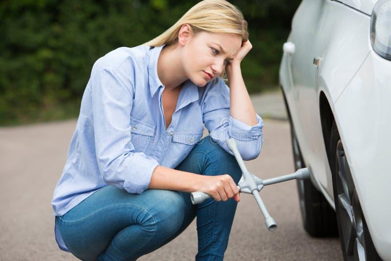 Motorista fêmea frustrante With Tire Iron que tenta à roda de mudança imagem de stock royalty free