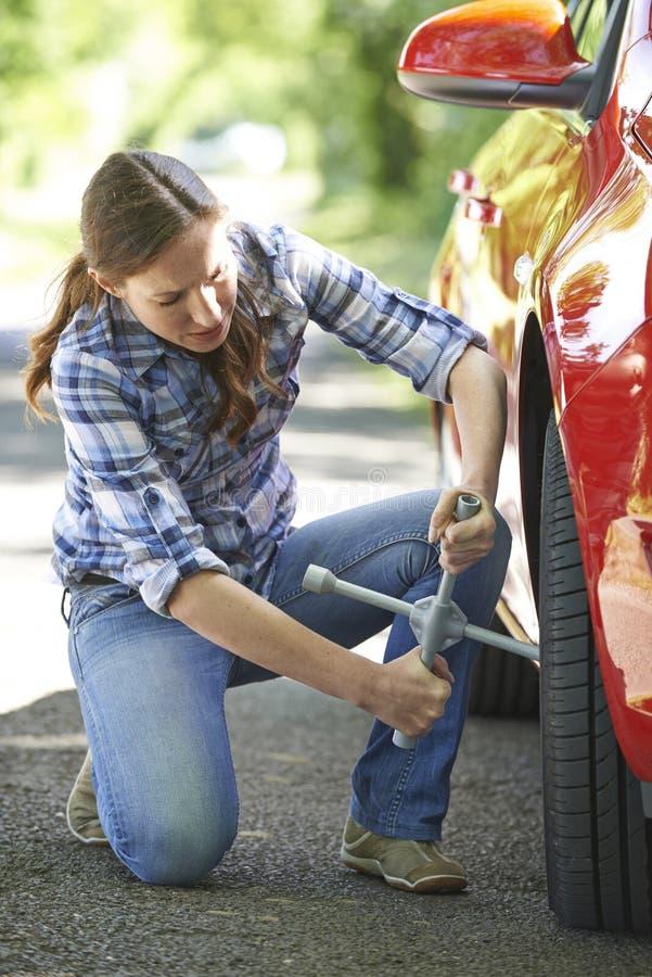 Motorista fêmea frustrante With Tyre Iron que tenta à roda de mudança fotografia de stock royalty free