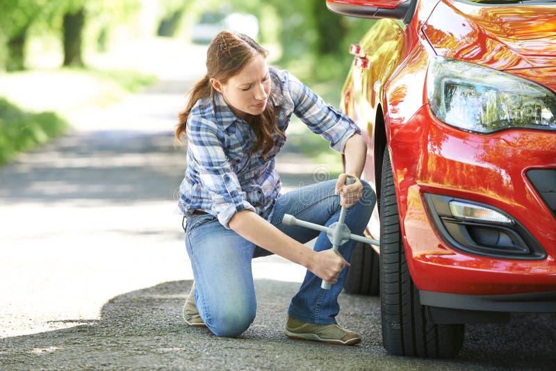Motorista fêmea frustrante With Tyre Iron que tenta à roda de mudança fotografia de stock