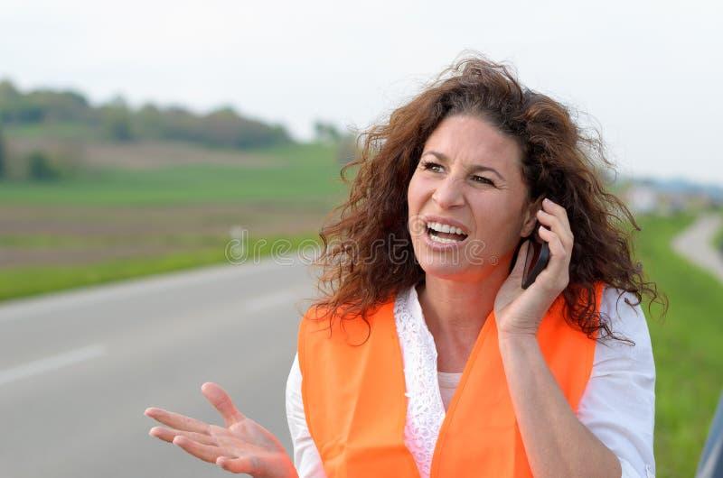 Motorista fêmea novo exasperado em seu móbil foto de stock