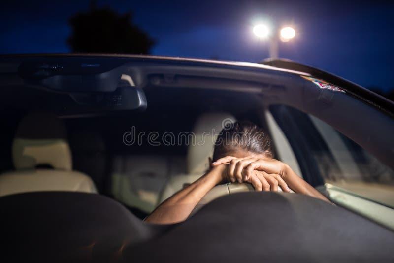 Motorista fêmea novo na roda de seu carro, cansado super foto de stock