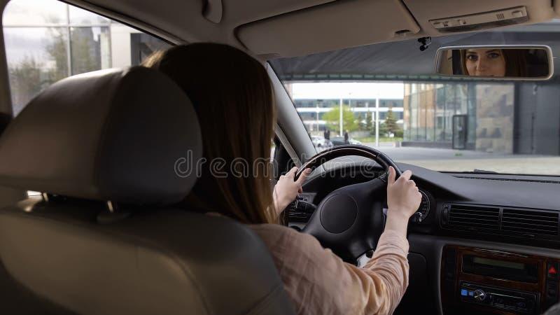 Motorista fêmea que senta-se no carro, olhando no espelho, levantando para a câmera, vista traseira imagens de stock royalty free