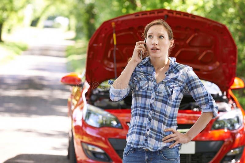 Motorista fêmea que telefona para a ajuda após a divisão imagens de stock royalty free