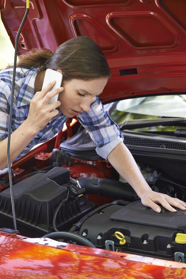 Motorista fêmea que telefona para a ajuda após a divisão fotos de stock