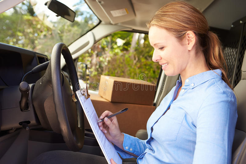 Motorista fêmea Sitting In Van Filling Out Paperwork da entrega imagem de stock