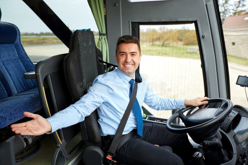 Motorista feliz que convida a bordo do ônibus interurbano fotografia de stock royalty free