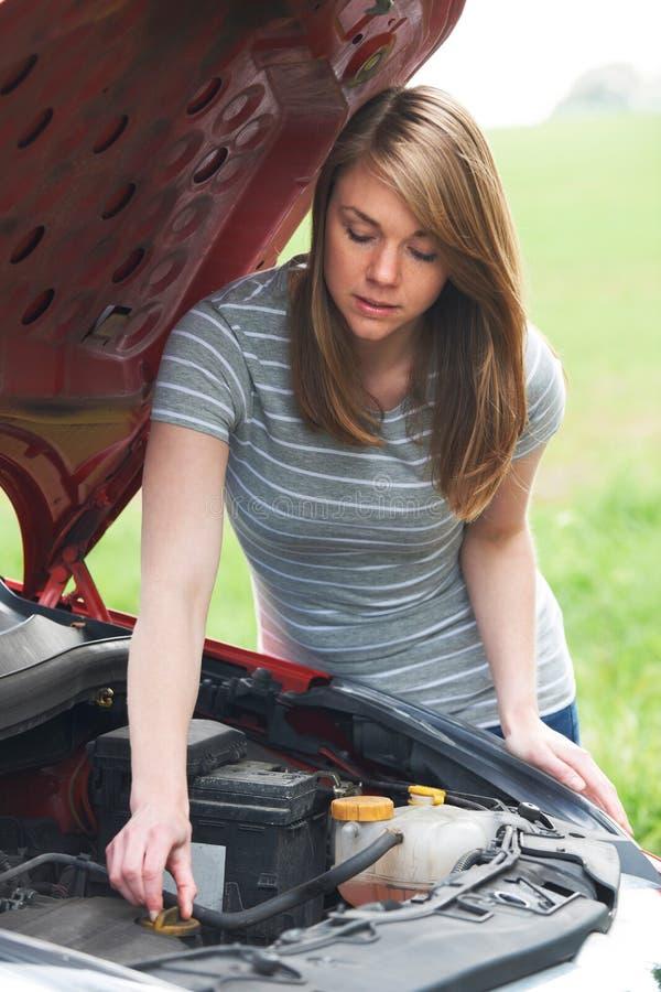 Motorista femenino analizado que mira el motor de coche imagen de archivo libre de regalías