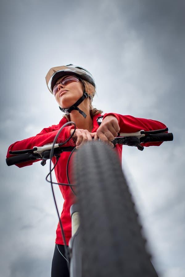Motorista femenino bonito, joven al aire libre en su bici de montaña fotografía de archivo