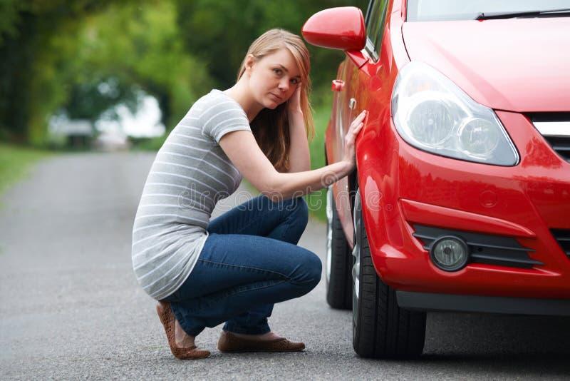Motorista femenino joven con puntura en la carretera nacional foto de archivo libre de regalías