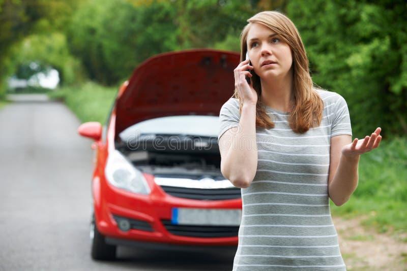 Motorista femenino que llama por teléfono para la ayuda después de avería foto de archivo