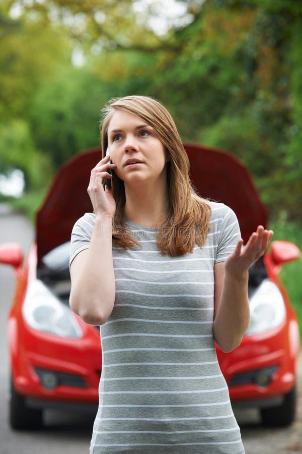 Motorista femenino que llama por teléfono para la ayuda después de avería imagen de archivo