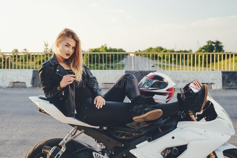 Motorista hermoso de la mujer que pone en una bici que se relaja foto de archivo