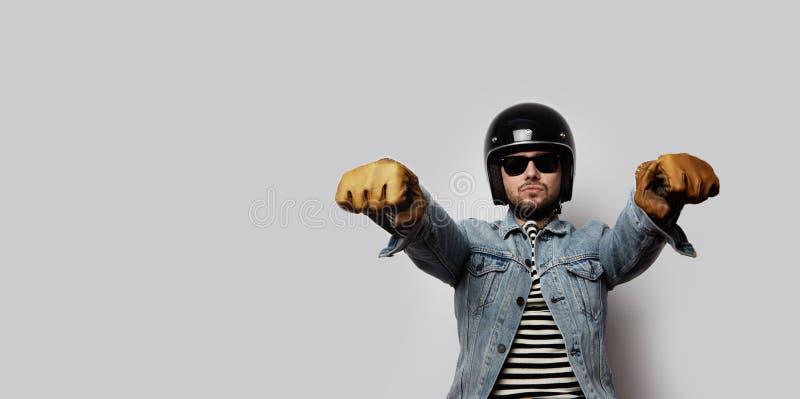 Motorista joven en una chaqueta azul del dril de algodón que finge montar una motocicleta aislada en el fondo blanco horizontal w imagen de archivo