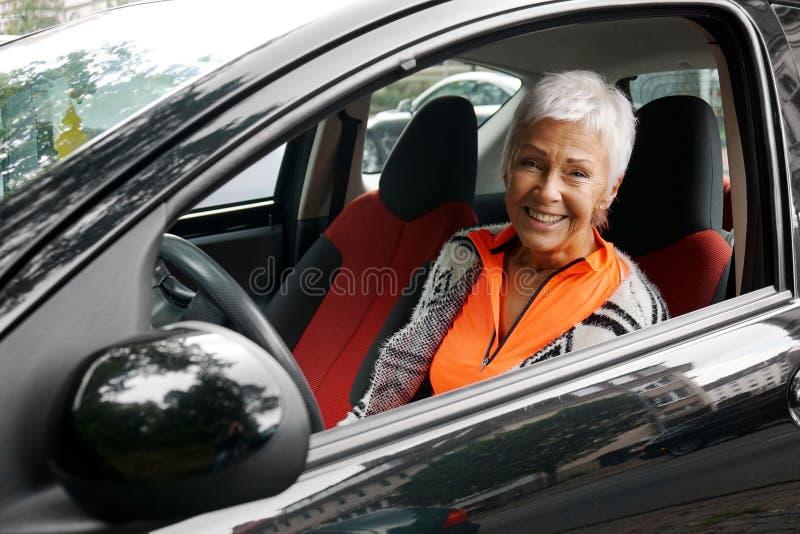 Motorista maduro da mulher em seu carro fotografia de stock