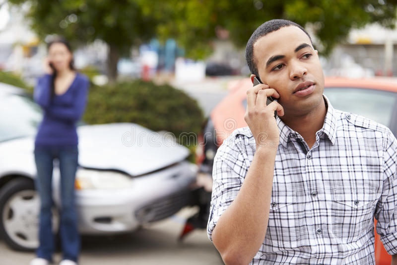 Motorista masculino Making Phone Call após o acidente de tráfico foto de stock