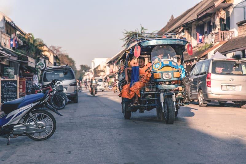 Motorista no tuk-tuk estacionado sobre ao levar a monge nova fotografia de stock