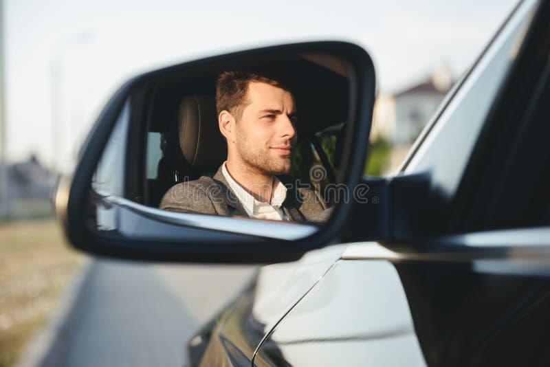 Motorista novo considerável feliz do homem de negócio em seu carro fotografia de stock royalty free