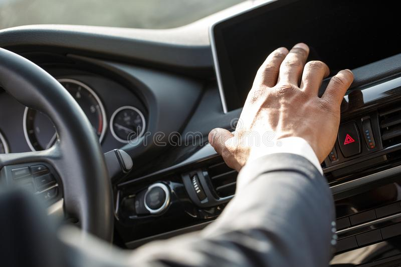 Motorista novo do homem de negócios que senta-se dentro do carro usando o close-up esperto da tela do controle imagem de stock royalty free