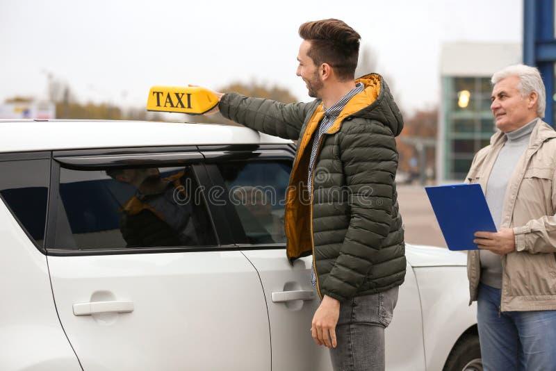 Motorista novo que põe a luz do táxi sobre o telhado do carro fotografia de stock royalty free