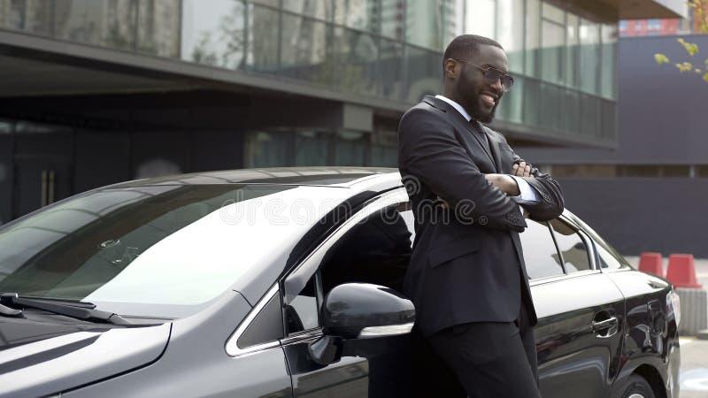 Motorista pessoal da pessoa importante no carro chique, amando e apreciando seu trabalho fotos de stock royalty free