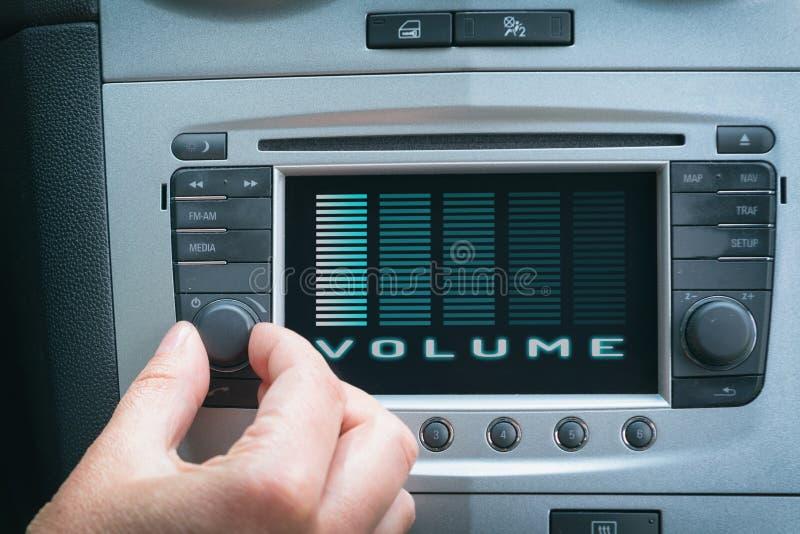 Motorista que ajusta o volume no sistema de áudio do carro fotos de stock