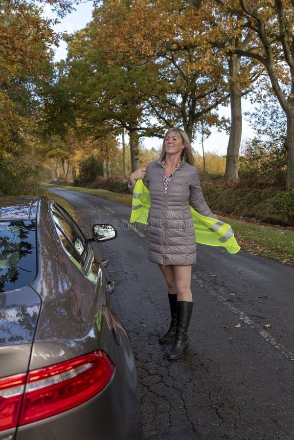 Motorista que põe sobre um revestimento reflexivo na borda da estrada fotografia de stock royalty free
