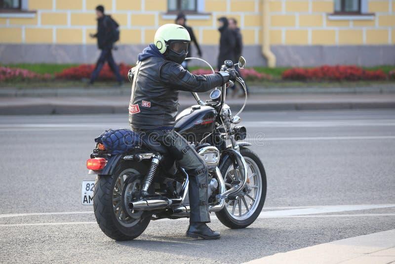 Motorista que se sienta en su motocicleta Harley-Davidson Sportster fotografía de archivo libre de regalías