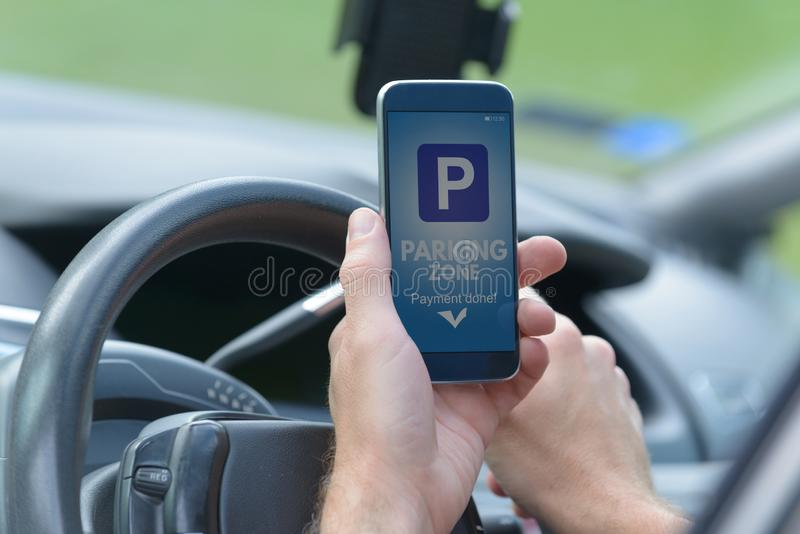 Motorista que usa o app do smartphone para pagar estacionar fotos de stock royalty free