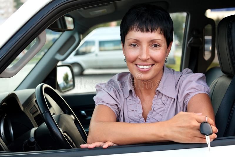 Motorista superior da mulher que guarda uma chave imagem de stock royalty free
