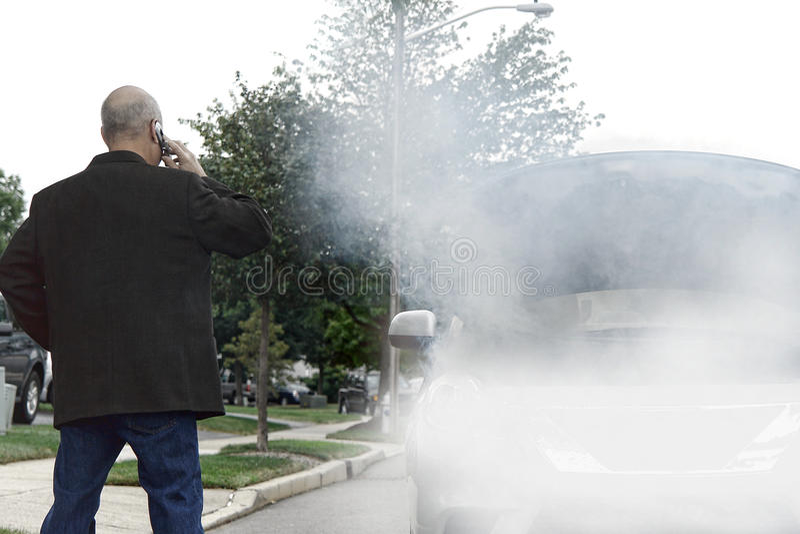 Motorista trenzado que llama ayuda con humo en coche imagenes de archivo