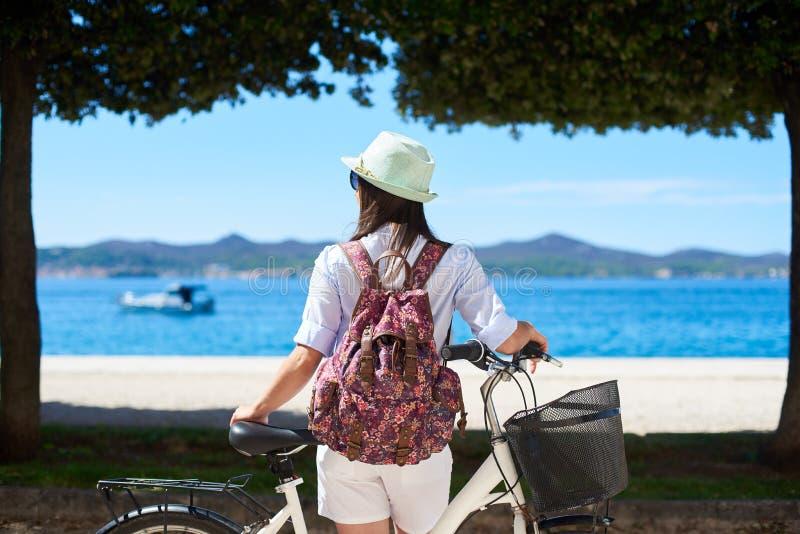 Motorista turístico de la mujer joven con la bicicleta de la ciudad en la ciudad cerca del mar imagen de archivo libre de regalías
