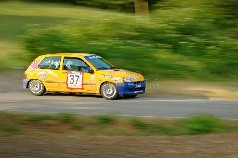 Motoristas não identificados em um carro de competência amarelo de Renault Clio do vintage fotografia de stock