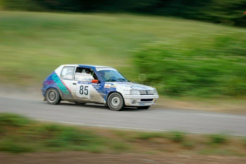 Motoristas não identificados em um carro de competência branco e azul de Peugeot 105 do vintage imagens de stock