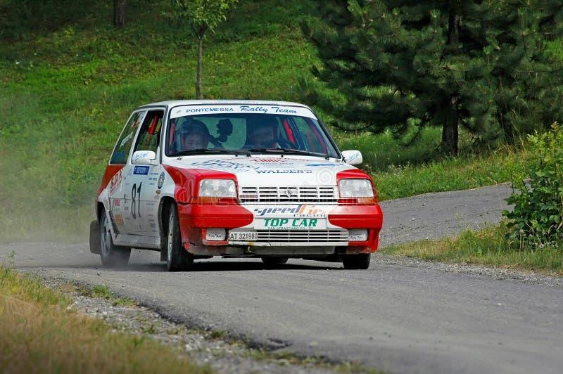 Motoristas não identificados em um carro de competência branco e vermelho de Renault 5 do vintage foto de stock royalty free