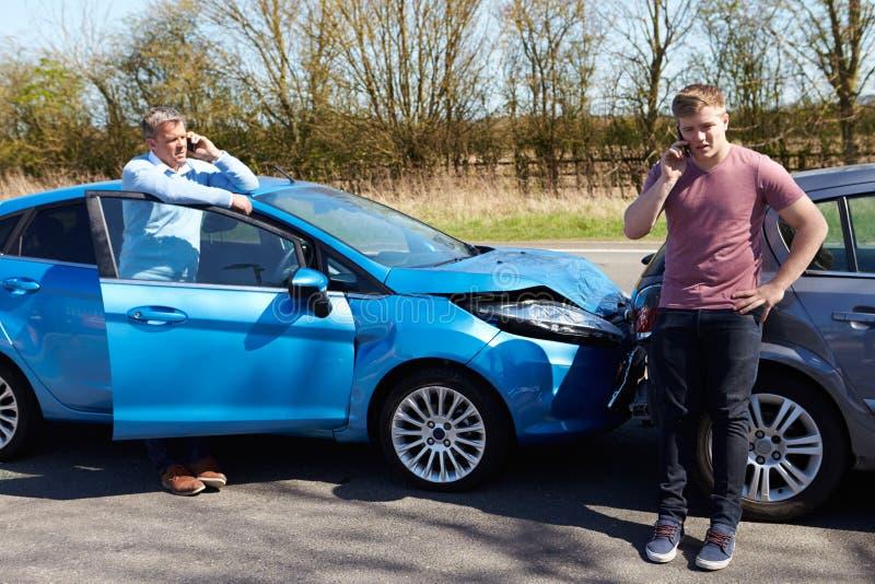 Motoristas que fazem o telefonema após o acidente de tráfico imagens de stock