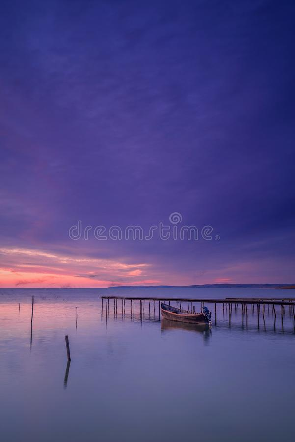 Motorized fishing boat near a pontoon captured before sunrise with  shadows of flying birds due to long exposure stock photography