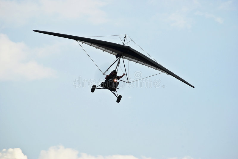 Motorized Hang Glider in Flight 02. Motorized Hang Glider in Flight. Microlight flying is an adventure sport that provides people of all ages with one of the stock images