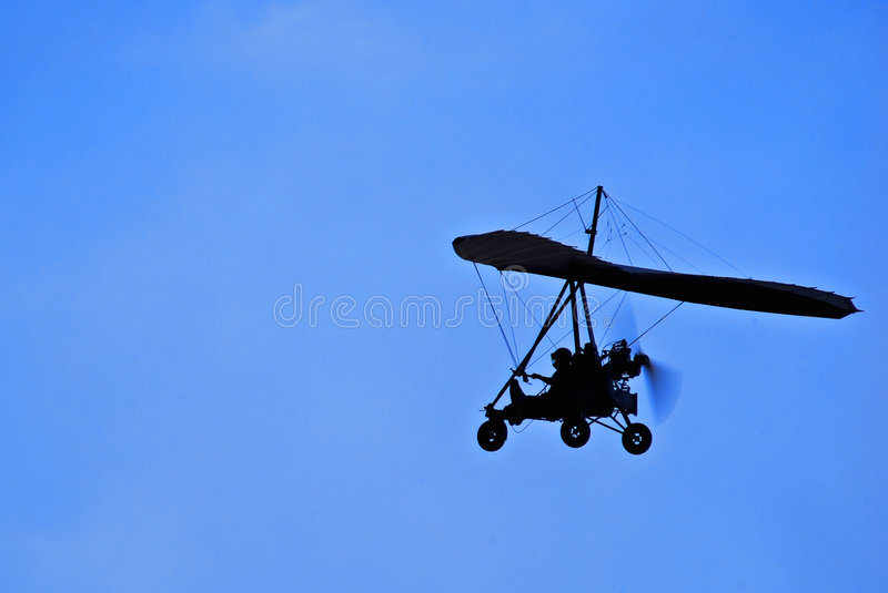 Motorized Hang Glider in Flight - Side On. Motorized Hang Glider in Flight. Microlight flying is an adventure sport that provides people of all ages with one of royalty free stock photo