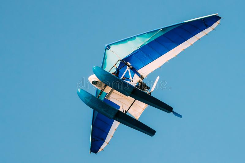 Motorized Hang Glider Flying On Blue Clear Sunny Sky Background royalty free stock images