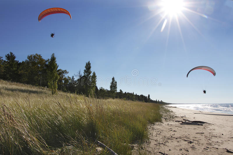 Motorized Hang Glider Kites Flying Over Secluded Beach. Two Motorized Hang Glider Kites Being Piloted Over Secluded Lake Huron Beach - Grand Bend, Ontario royalty free stock images