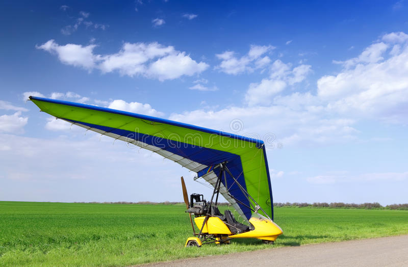 Motorized hang glider over green grass. Ready to fly royalty free stock photos
