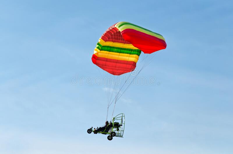 Motorized paraglider flying high in sky from side view. Man taking a ride in the sky with his motorized paraglider stock photos